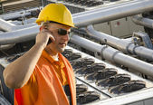 Worker with helmet and sunglasses talking on mobile phone in front of cooling plant — Stockfoto