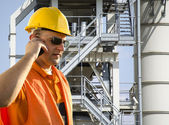 Worker with helmet and sunglasses talking on mobile phone in front of industrial plant — Stock Photo