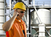 Worker with helmet and sunglasses talking on mobile phone in front of oil plant — Stock fotografie