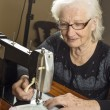 Stock Photo: Older womworking on sewing machine