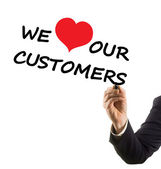 Businessman hand writing text we love our customers — Stok fotoğraf
