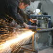 Stock Photo: Manual worker grinding steel table in production hall