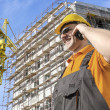 Worker in front of construction site talking on smart phone — Stock Photo