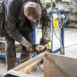 Stock Photo: Worker grinding steel table