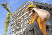 Trabajador frente construcción hablando por teléfono inteligente — Foto de Stock