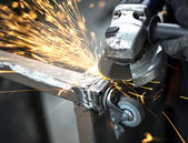 Manual worker grinding steel table in production hall — Stock Photo