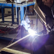 Stock Photo: Manual worker welding metal table in production hall