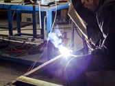 Manual worker welding metal table in production hall — Stock Photo