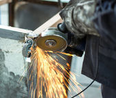 Worker grinding steel table in production hall — Stock Photo