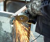 Werknemer slijpen stalen tabel in productiehal — Stockfoto