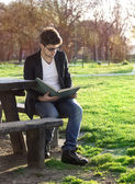 Teenager reading book in park — Stock Photo