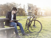 Teenager with bicycle reading book in park — Stok fotoğraf