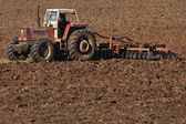 Huge tractor collecting haystack in the field at nice blue sunny — Стоковое фото