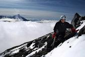 Hiker on mountain with peak on fog — Stock Photo