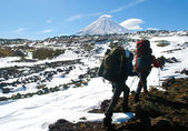 Two hikers walking in snow mountains — Stock Photo