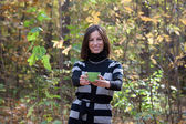 Young lady with green cup of tea in autumn forest — Stock Photo