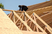 A roofing contractor installing rafters at a commercial residential development. — Stock Photo