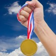 Golden medal in man's hand isolated on white background. — Stock Photo