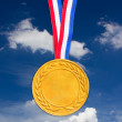 Golden medal in front of blue sky. — Stock Photo