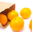 Oranges falling from paper bag, isolated on white background. — Stock Photo