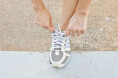 The girl tying running shoes — Stockfoto