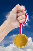 Golden medal in woman's hand isolated on white background. — Stockfoto