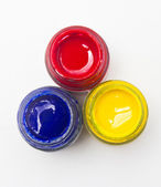 Top view of opened bottles of primary color on white background. — Stock Photo