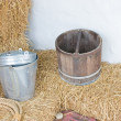 Metallic bucket and wooden bucket on rice hay. — Stock Photo