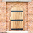 Closed wooden door with brick wall. — Stock Photo