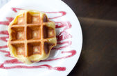 Close up of waffle on white plate with grape sauce. — Stock Photo