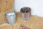 Metallic bucket and wooden bucket on rice hay. — Stock Photo