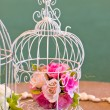 Artificial flowers bunch in birdcage. — Stock Photo