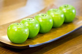 Plastic green apples on plate. — Stockfoto