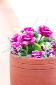 Colorful artificial flowers in clay pot. — Stock Photo
