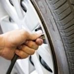 Man's hand checking tyre pressure. — Stock Photo #32688821