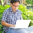 Asian man working with laptop — Stock Photo