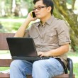 Asian man talking on phone and using laptop. — Photo