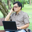 Asian man with mobile phone working with laptop — Stock Photo