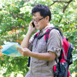 Asian man with mobile phone and map — Stock Photo