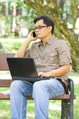 Hombre asiático hablando por teléfono y el uso del ordenador portátil. — Foto de Stock