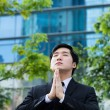 Asian Businessman praying for success — Stock Photo