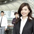 Business woman with colleagues in the background — Stock Photo