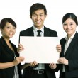 Business team holding a blank sign — Stockfoto