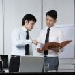 Two Chinese businessmen reading a file — Stock Photo