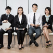 Stock Photo: Happy Chinese business team sitting in a row.