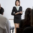 Chinese Business woman giving presentation with touchpad — Stock Photo