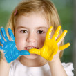 Little girl with hands painted - Stock Photo
