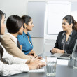 Stock Photo: Serious boss talking with her team.