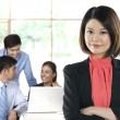 Chinese Business woman with colleagues in the background out of — Stock Photo