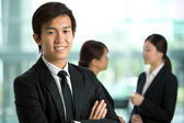 Asian Business man with colleague's in background — Stock Photo